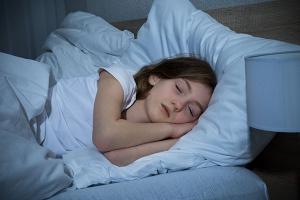 Girl Sleeping On Bed In Dark Bedroom